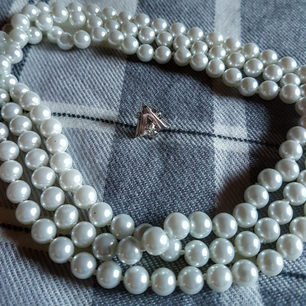 Alpha Gamma Delta badge with pearl necklace